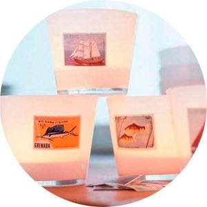 """Если не сможете отыскать в магазине готовые свечи в """"курортном"""" стиле, наклейте на обычные стаканы картинки изображениями на морскую тематику."""